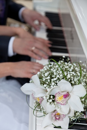 Hands young on keys and a wedding bouquet Stock Photo