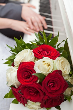 Hands young on keys and a wedding bouquet photo