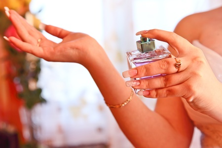 Bottle of perfume in hands of the girl