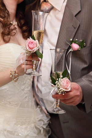 buttonhole: Wine glasses with champagne in hands of the groom and the bride Stock Photo
