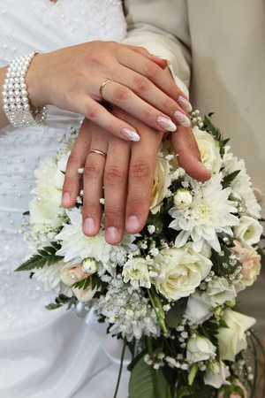 Hands of a newly-married couple on a bunch of flowers