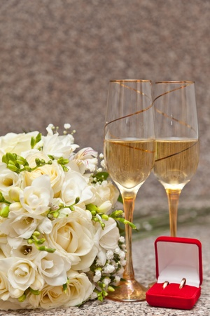 Wedding bouquet, wine glasses with champagne and wedding rings photo