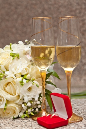 Wedding bouquet, wine glasses with champagne and wedding rings