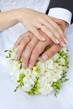 c�r�monie mariage: Mains avec des anneaux de mariage et un bouquet de mariage