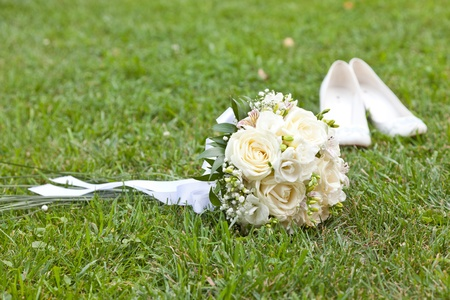 Wedding bouquet and shoes on a green grass photo