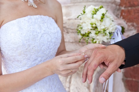 The bride dresses a ring on a hand to the groom Stock Photo