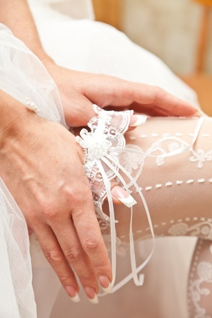 Garter on a foot of the bride photo