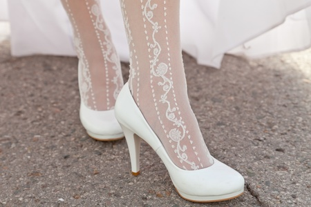 Feet of the bride in white shoes photo