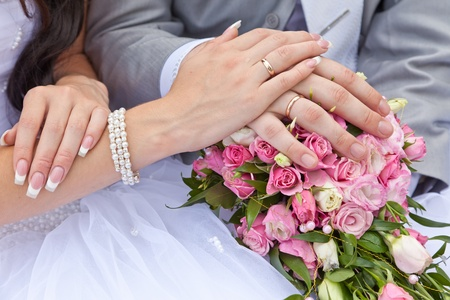 Hands of a newly-married couple with rings on a wedding bouquet Archivio Fotografico
