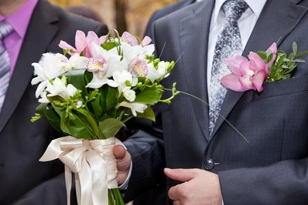 Wedding bouquet in hands of the groom photo