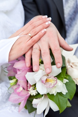 Hands of the groom and the bride with wedding rings on a wedding bouquet