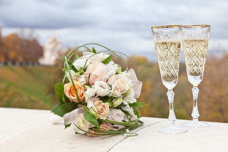 Wedding bouquet and wine glasses with champagne photo