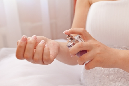 A bottle of perfume in the hands of the bride