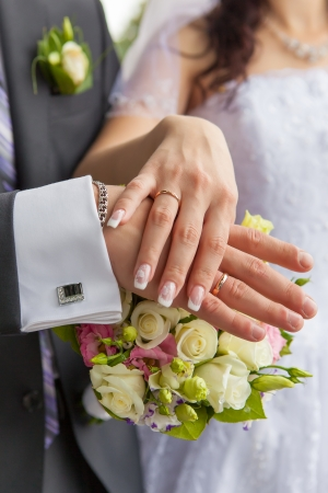 Hands with wedding rings and a wedding bouquet