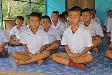 UDONTHANI, THAILAND – MAY 16, 2018:  Students,  sit for training the concentrate,  be morality of Buddhism,  that they do everyday before study in afternoon.