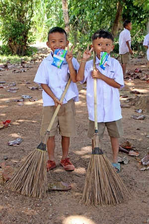 UDONTHANI, THAILAND – JUNE 13, 2018: Asia students, two boys are sweeping dry leafs with broom, be their activity in the morning everyday, see them at BAN HUA KUA MUEAD AE school.