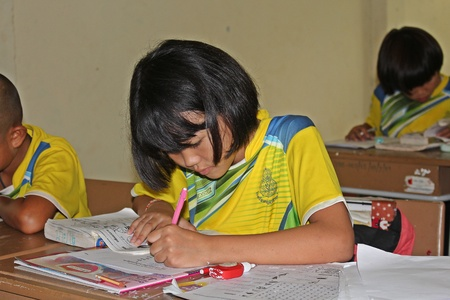 UDONTHANI, THAILAND – JUNE 21, 2018:  Asian student,  Asian student is writing,  be tests by her teacher,  see her in BAN HUA KUA MUEAD AE school,  at UDONTHANI province THAILAND. Editorial