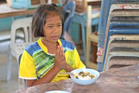 UDONTHANI, THAILAND – AUGUST 9, 2018:  Asian student, she is praying,  be the activity before have lunch everyday,  see her in BAN HUA KUA MUEAD AE school at UDONTHANI province THAILAND.