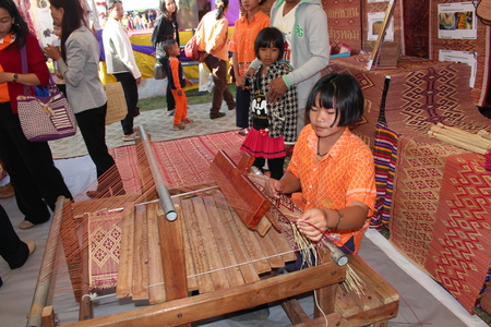 SURIN, THAILAND – JULY 10, 2018:  Asian girl is weaving the mat for show to people,  the mat is cheap goods,  see her at SURIN province THAILAND. Editorial