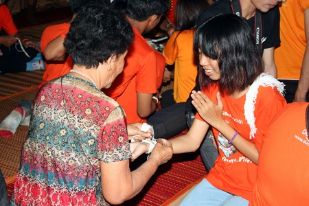 UDONTHANI, THAILAND – SEPTEMBER 1, 2018:  Thai student,  elder is binding the wrist and blesses to Thai student,  after she ends Undergraduate course,  see her at UDONTHANI province THAILAND.