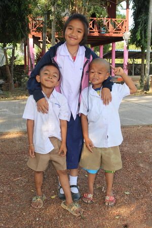 UDONTHANI, THAILAND – DECEMBER 12, 2018 :  Two boys and one girl pose for take a photograph,  see them at in front of school building,  in UDONTHANI province THAILAND.