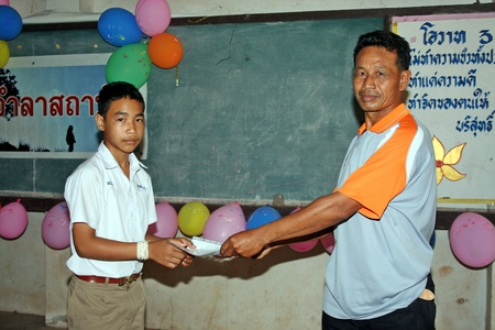 UDONTHANI, THAILAND – MARCH 22, 2018 :  Asian student is taking educational diploma from his teacher,  that day he end the education in this school,  see him at BAN NONG WANG NON KHI LEK school.