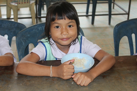 UDONTHANI, THAILAND – JANUARY 28, 2019:  Lunch time,  Thai student is enjoy in lunch time at her school,  see her at BAN HUA KUA MUEAD AE school.