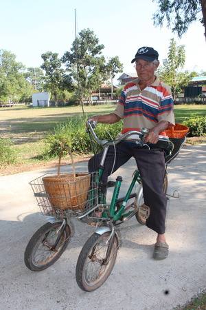 UDONTHANI, THAILAND – FEBRUARY 5, 2019 :  Asia man, one man riding a bicycle in school area,  he takes something for sell to teacher. Editoriali