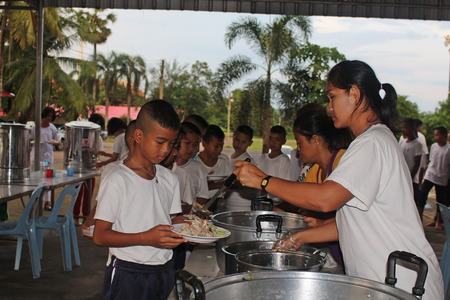 UDONTHANI, THAILAND – SEPTEMBER 20, 2019 : Asian students stand in row and be taking the lunch from woman cook, while they stay in moral camp at UDONTHANI province THAILAND.