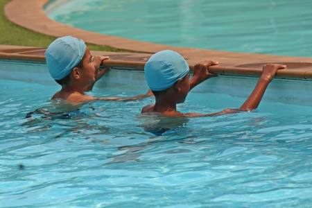 UDONTHANI, THAILAND – OCTOBER 4, 2019:  Asian children stay at rim of pool,  they are studying that way to swim from trainer,  see them in UDONTHANI province THAILAND. 에디토리얼