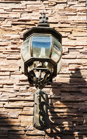 close up vintage street lamp style with LED lighter on brickwork wall its show the time of sunset with shadow distant  photo