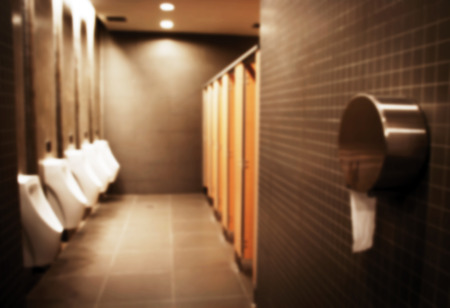 blurry silhouete toilet men room in brown interior photo