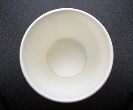 buttom: cllose up buttom of empty recycle paper cup on dark bacground texture