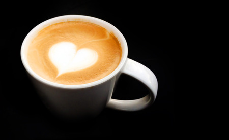 lighting cup of latte art coffee  on dark background photo