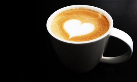 vivd lighting cup of latte art coffee  on dark background photo