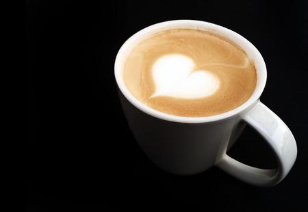 lighting cup of latte art coffee on the dark photo