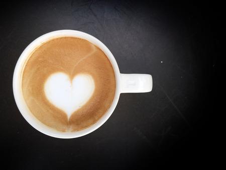 ligting cup of latte art coffee  on dark background photo