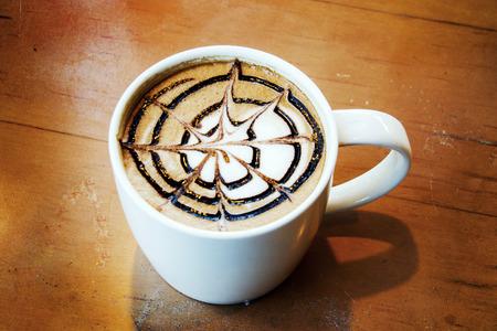 close up latte art splash line on ceramic mug on wood table photo