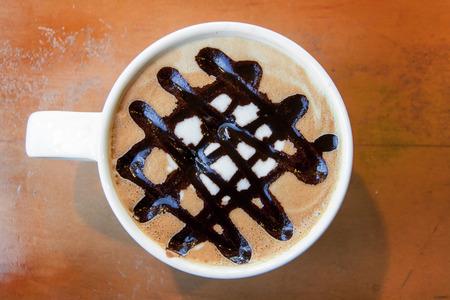 close up latte art net line on ceramic mug on wood table photo