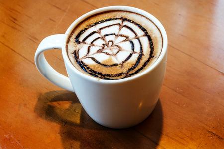 latte art design on ceramic mug on wood table photo