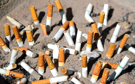 close up Cigarettes in outdoors ashtray with sand photo