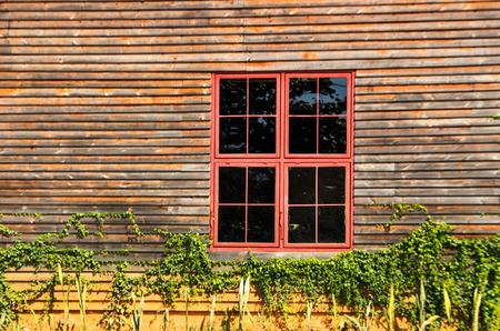 pannel: focus red metal windows on wood wall Stock Photo