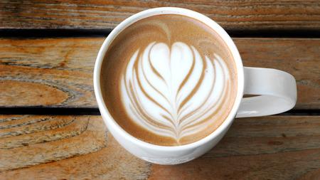 lattee art coffee cup on wood table photo
