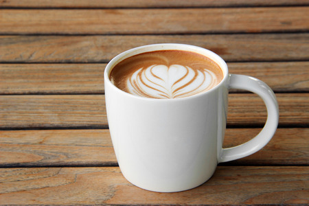 latte art in cup on wood table photo