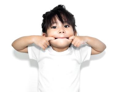 caras graciosas: close up asi�tica ni�a jugando su boca en la acci�n divertida