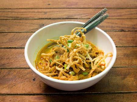 chinese food: Thai Food call Khao Sawy, Northern Thai Noodle Curry Soup on wood table