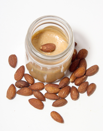 close up almond butter in glass bottle on isolate