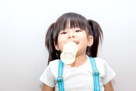 nursing bottle: asian kid smie action with her nursing bottle on white background