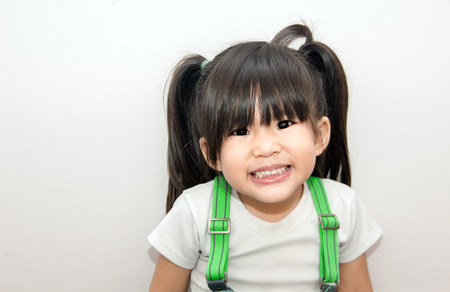 cute asain kid with pony tail smiling on white background