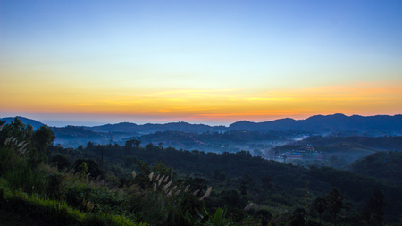 faintly visible: sunrise on the mountain and green grass flower with landscape Stock Photo